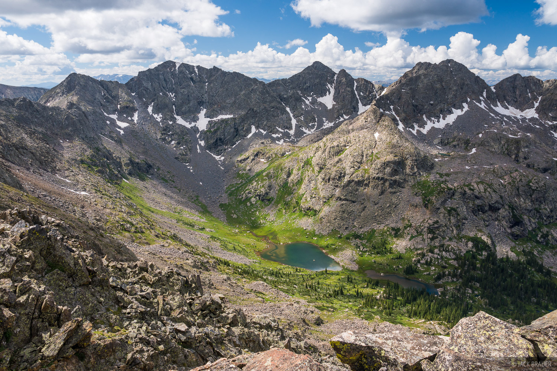 Looking down towards a remote alpine lake below rugged peaks deep in the Holy Cross Wilderness.