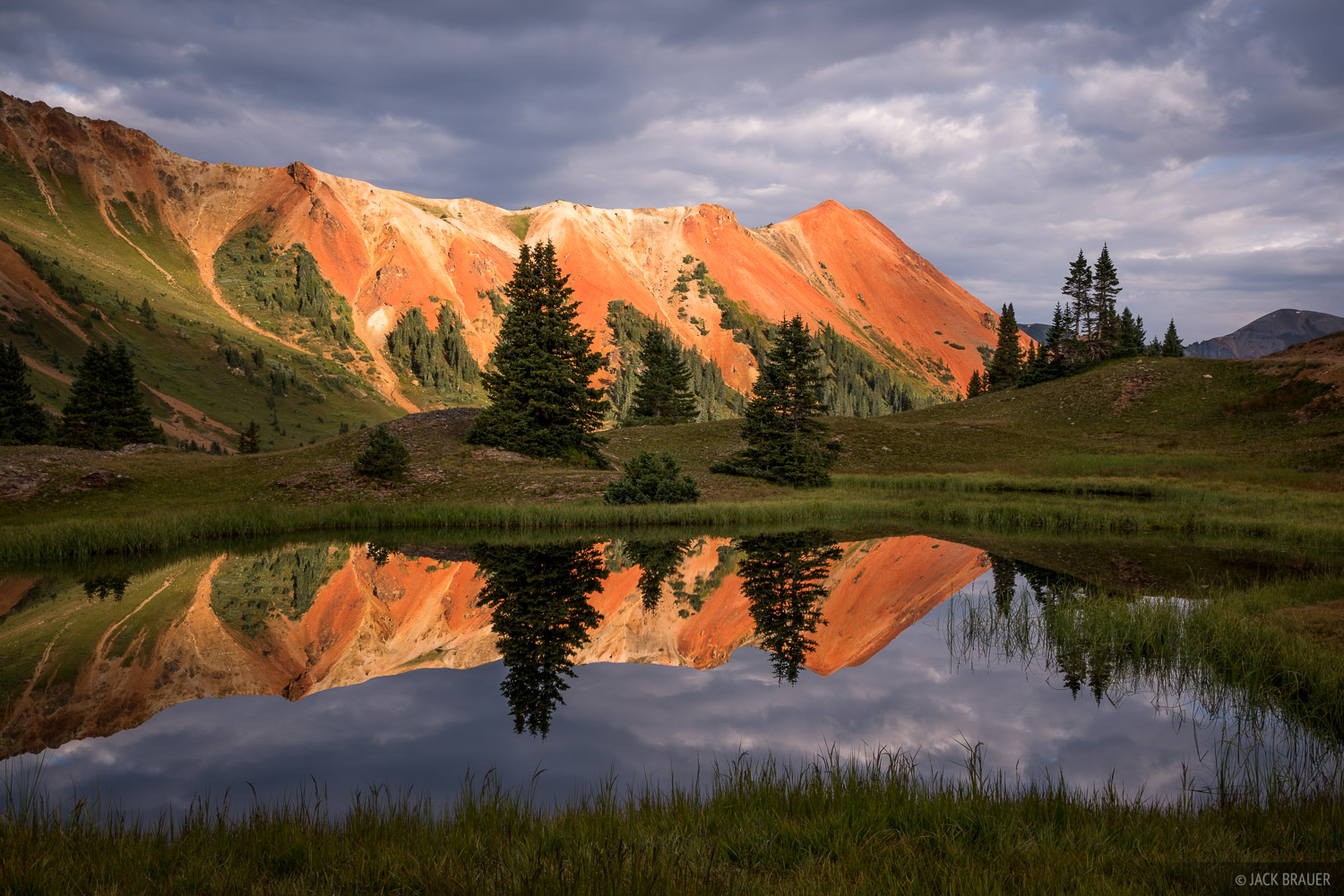 Red Mountain #1 reflects in an alpine tarn at sunrise.