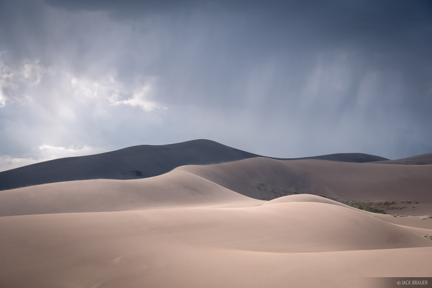 Thunderclouds and rain roll over the Great Sand Dunes.