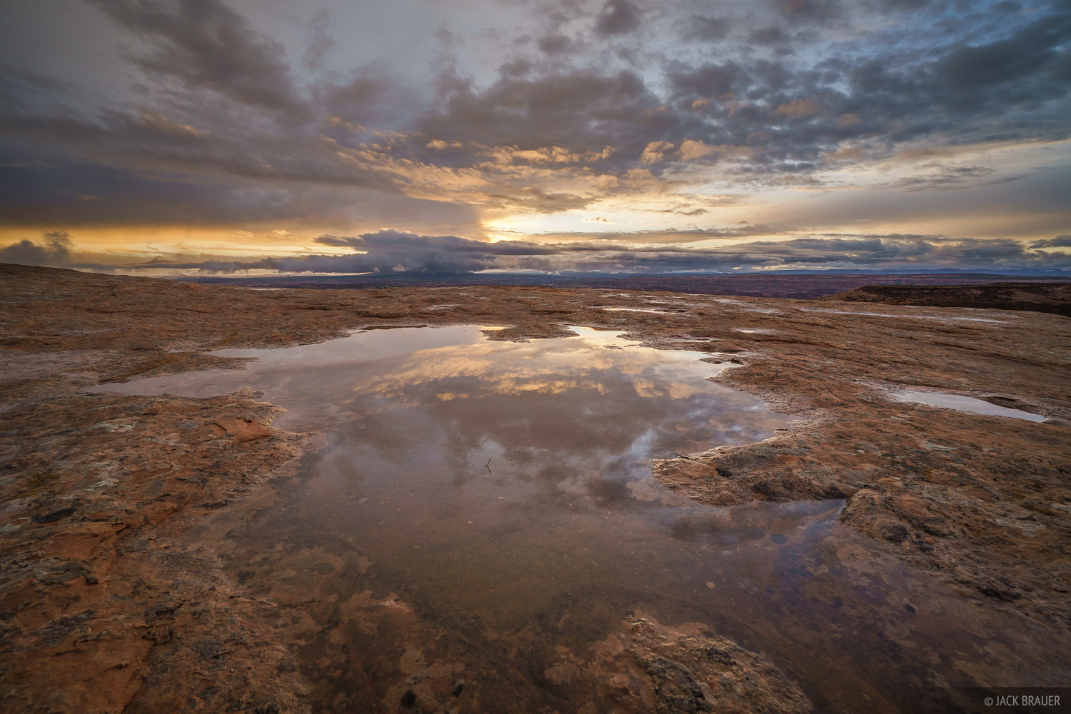 Sunrise reflection in a slickrock pothole after a rainy night in the desert.