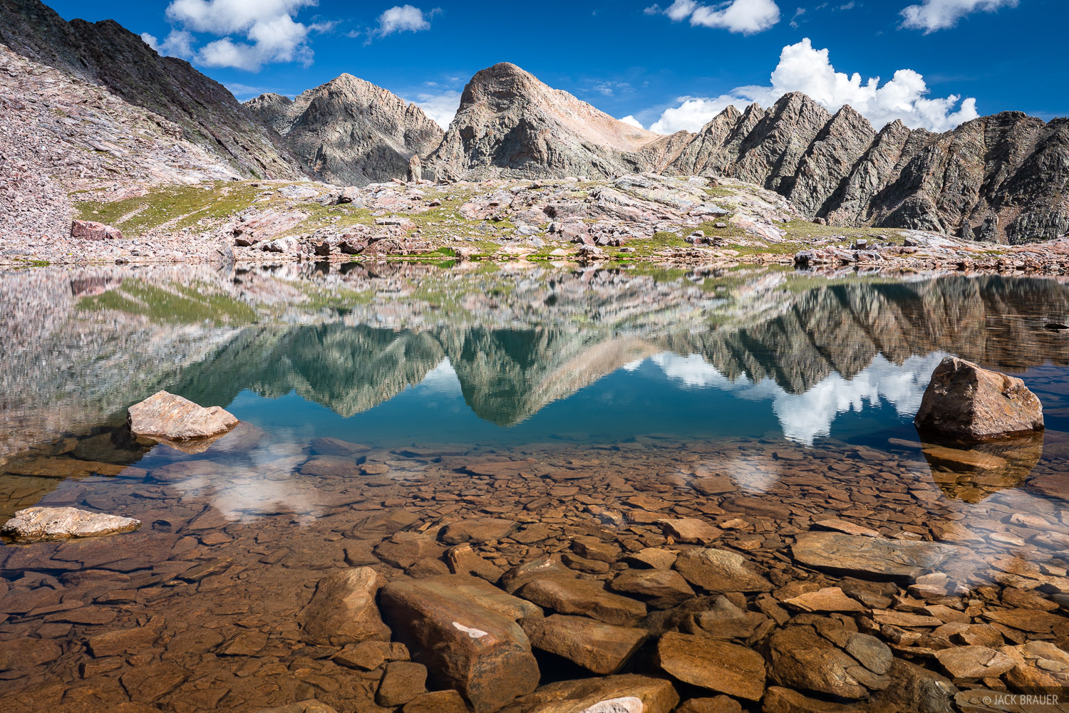 Trinity Peaks reflected in a high lake.