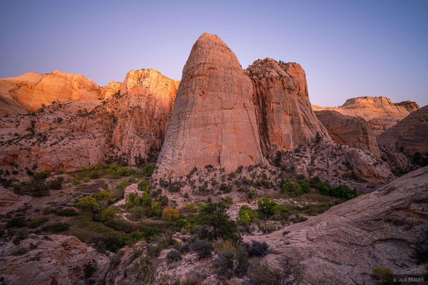 Huge sandstone walls in Death Hollow. The white sandstone glows a rich pinkish orange color in the dusk light after sunset.