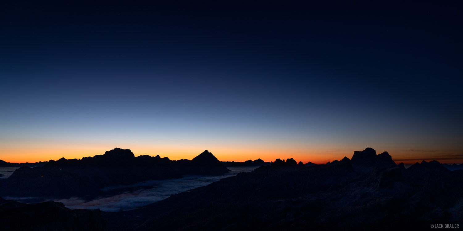 The first colors of dawn glow over Gruppo del Sorapis, Monte Antelao, and Monte Pelmo. Cortina d' Ampezzo is down in the valley...