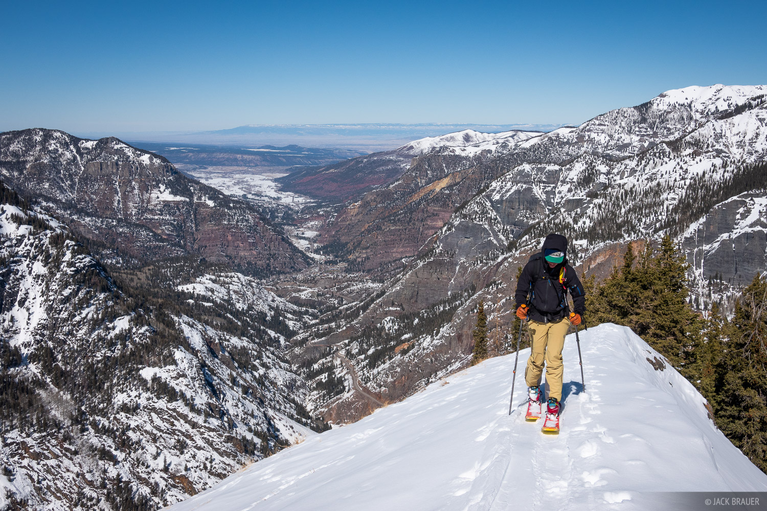 Nicole Skoloda skins up a ridge high above the town of Ouray. Grand Mesa is visible way off in the distance to the north.