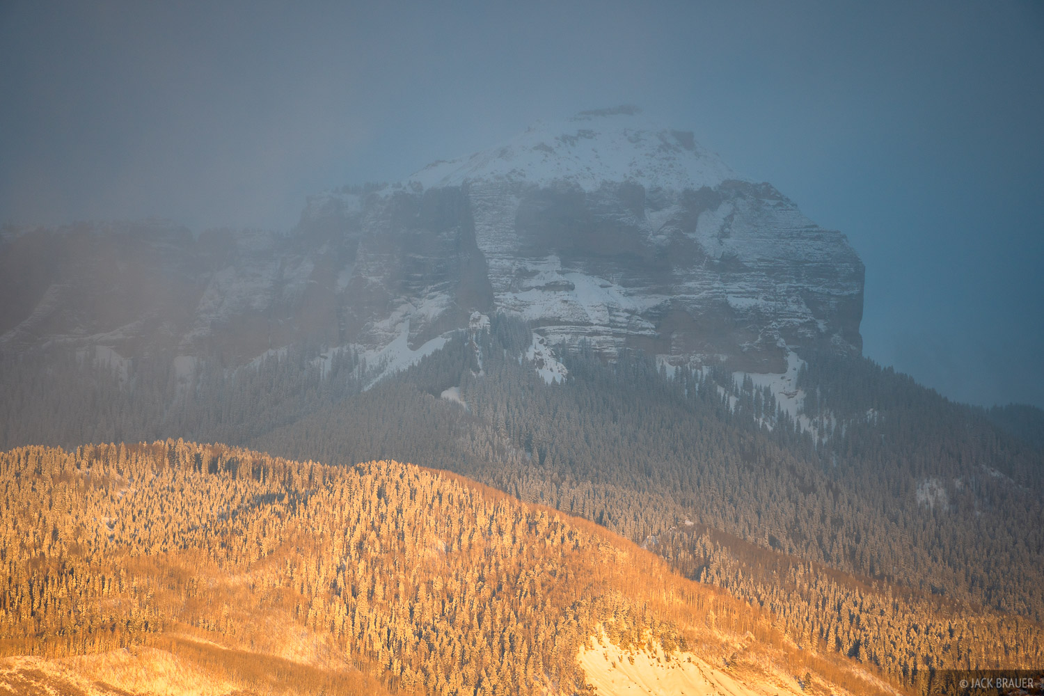 Evening light creeps up towards Courthouse Mountain, shrouded in a winter snowstorm.