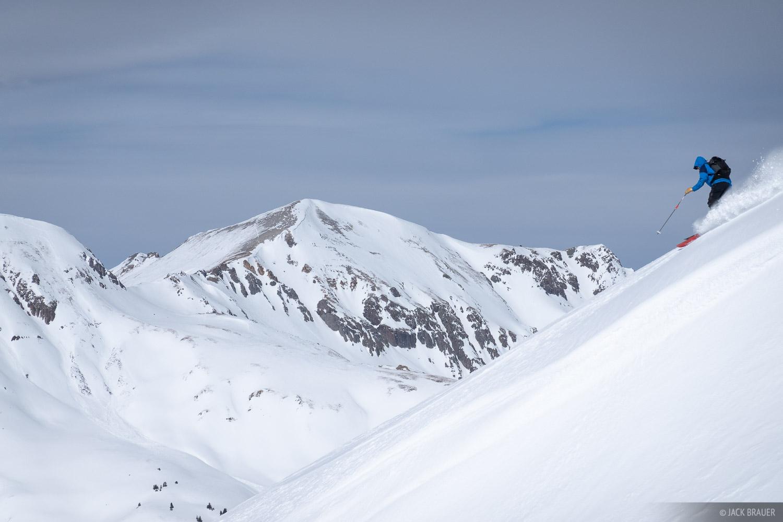 Unknown skier skis a ridgeline.