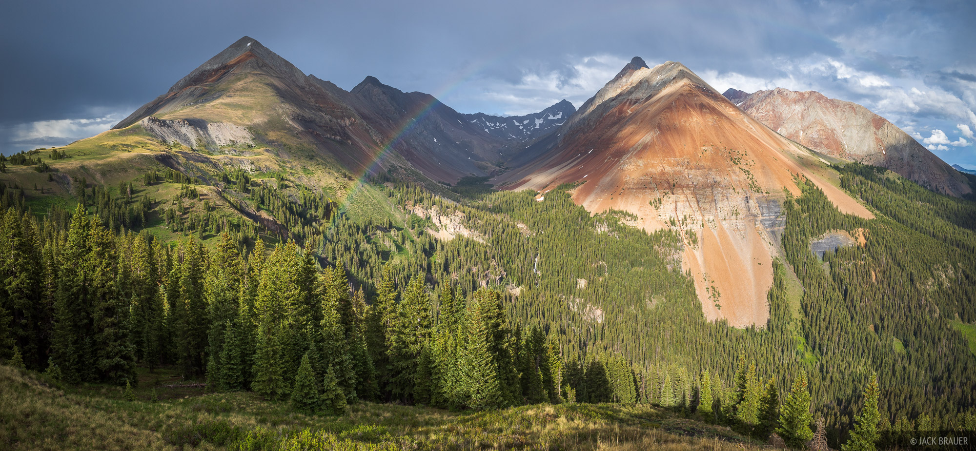 Sunlight on El Diente (14,159 ft.) as fleeting rainbow appears above the Navajo Lake basin, shortly after a thunderstorm passed...