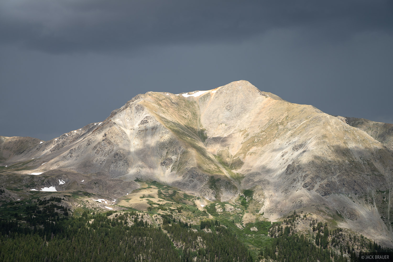 Sunlight shines on Mount Belford (14,197 ft.) with a dark thunderstorm behind. Lightning bolts were striking behind the peak...