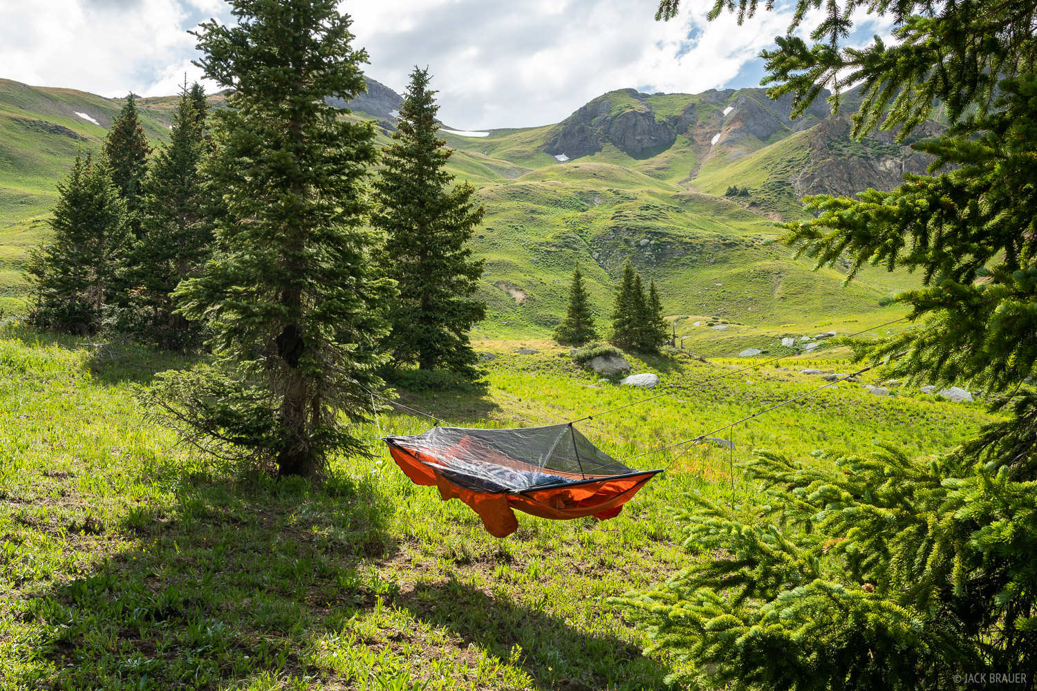 Hammock camp in a verdant green basin in the San Juan Mountains.