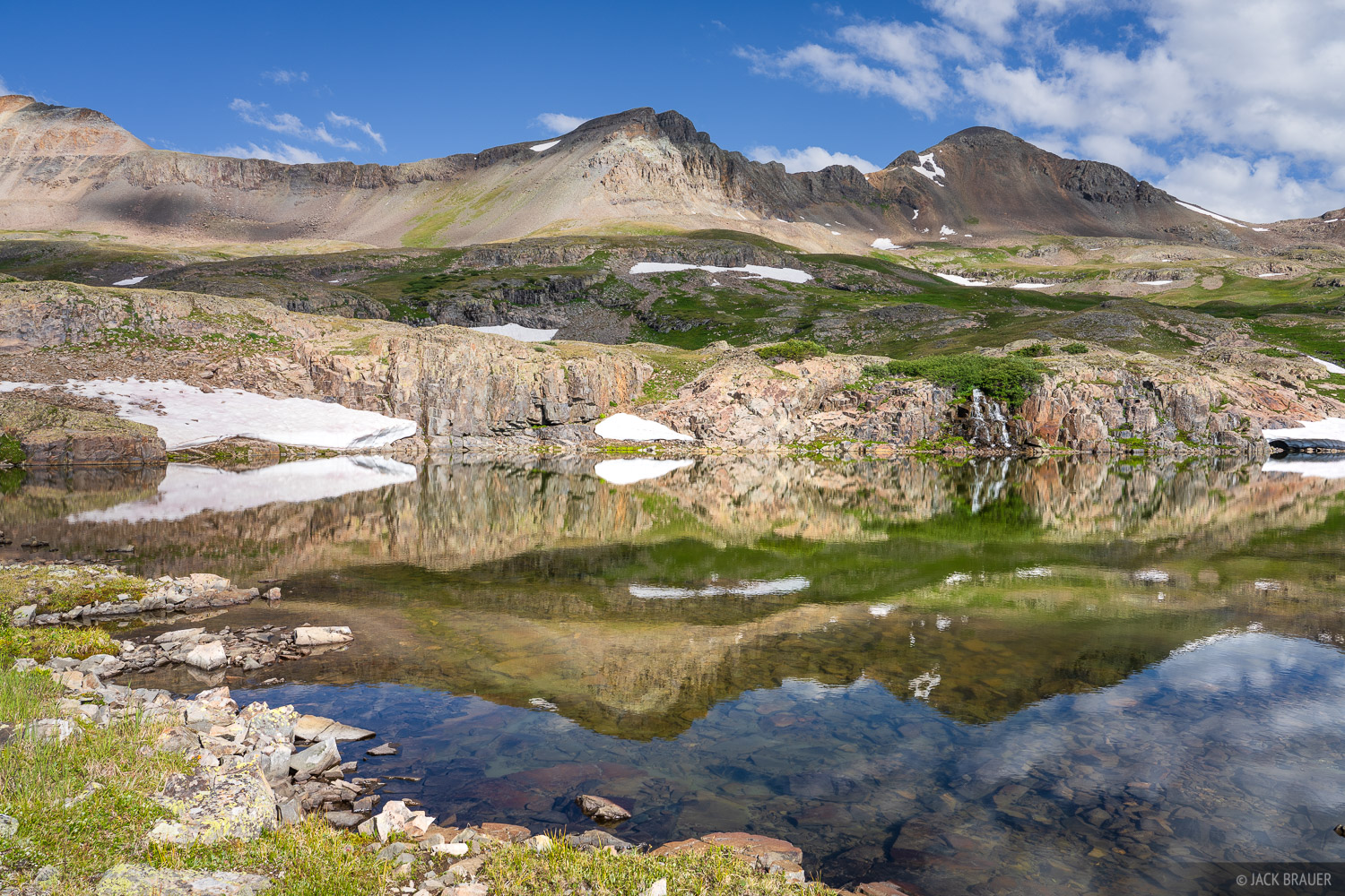 Cloud shadows reflected in a small alpine lake in the San Juan Mountains - July.