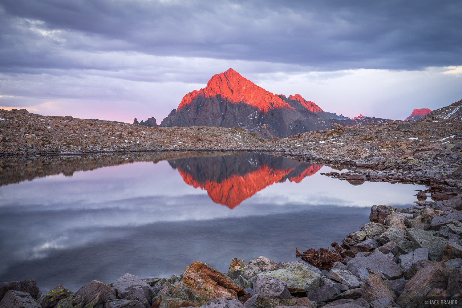 The last light of sunset pops through under the clouds, illuminating the summit of Mount Sneffels (14,150 ft).