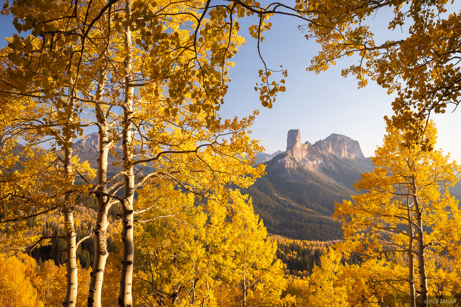 A view of Chimney Rock and Courthouse Mountain through a grove of aspens.