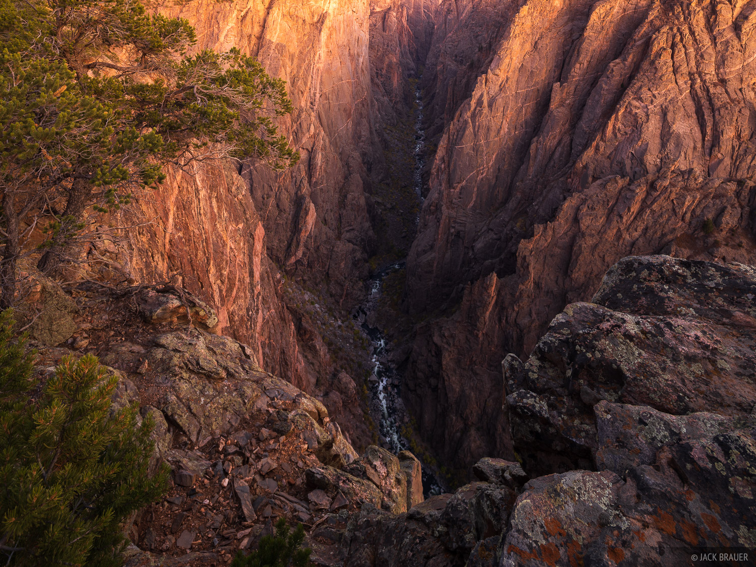 Glowing dusk light illuminates the walls of the Black Canyon after sunset, nearly 2,000 feet above the Gunnison River.