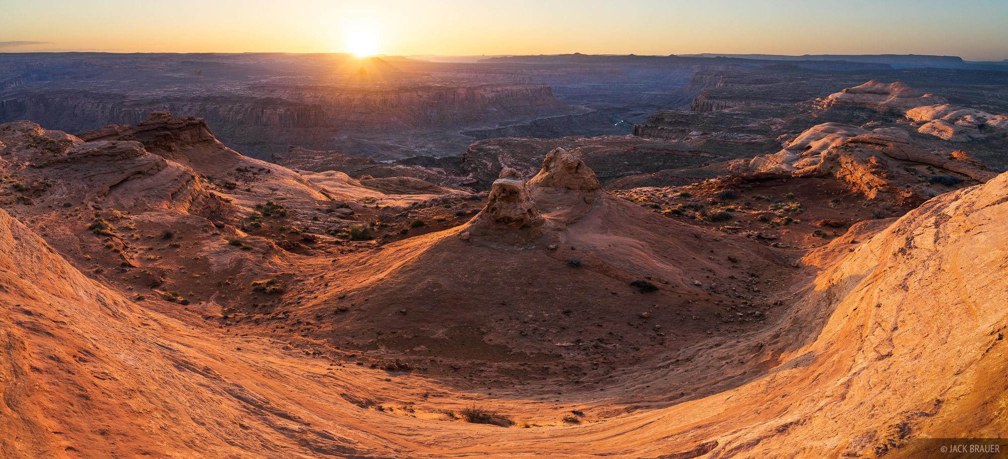 Sunrise light illuminates a slickrock bowl high above the Dirty Devil River.
