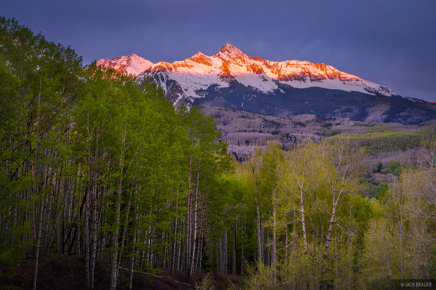 A brief moment of sunrise light illuminating Wilson Peak (14,016 ft.) on a cloudy spring morning in the San Juan Mountains near...