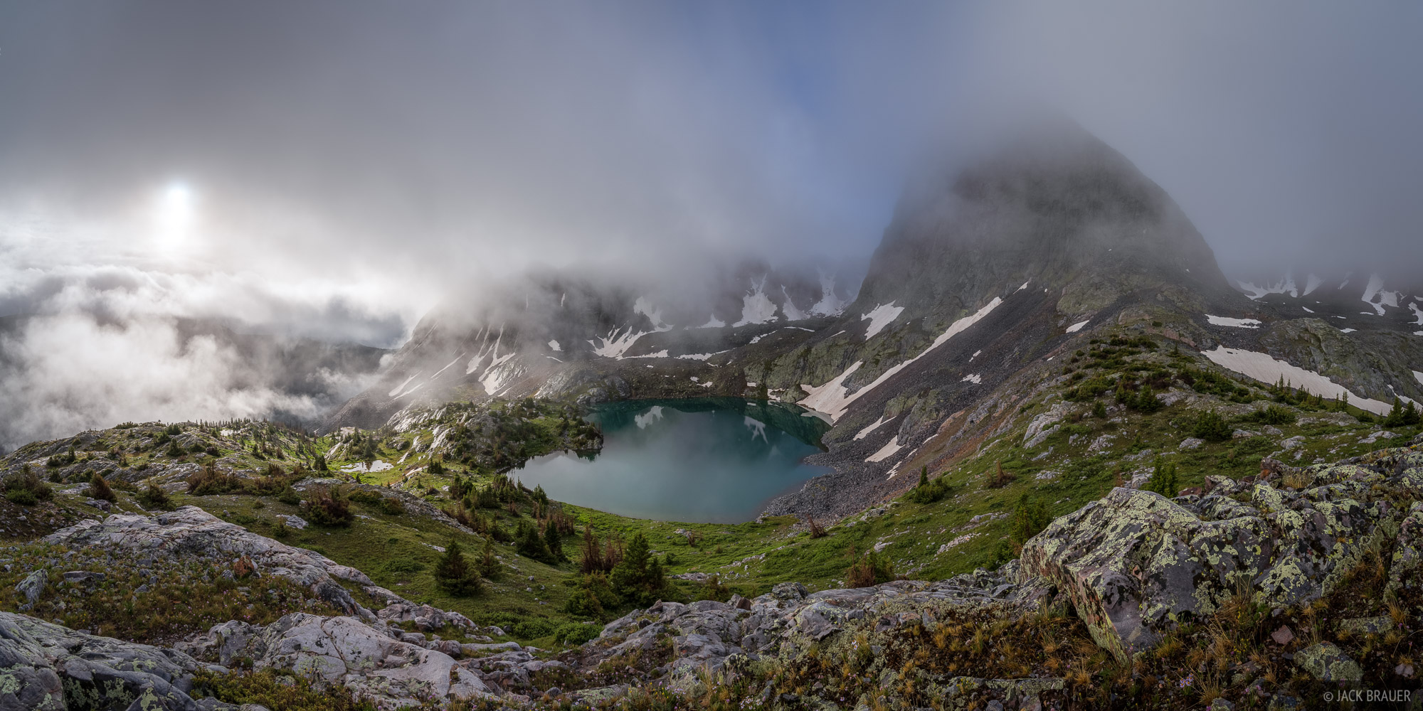 The morning sun pokes through rain clouds above a remote, unnamed lake deep in the Weminuche Wilderness.