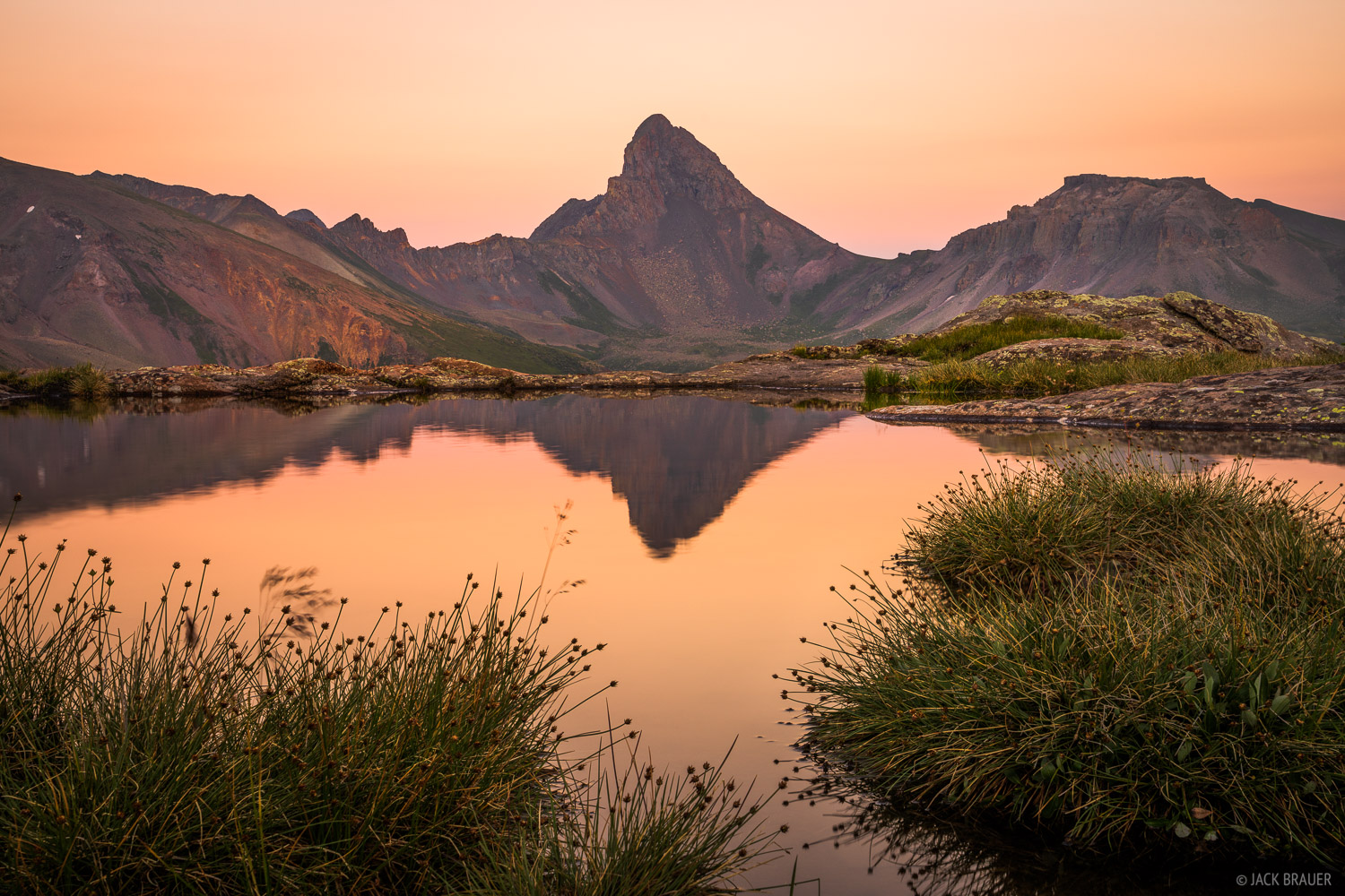 Sunset light illuminates a hazy sky above Wetterhorn Peak (14,015 ft.) in the San Juan Mountains of southwest Colorado.