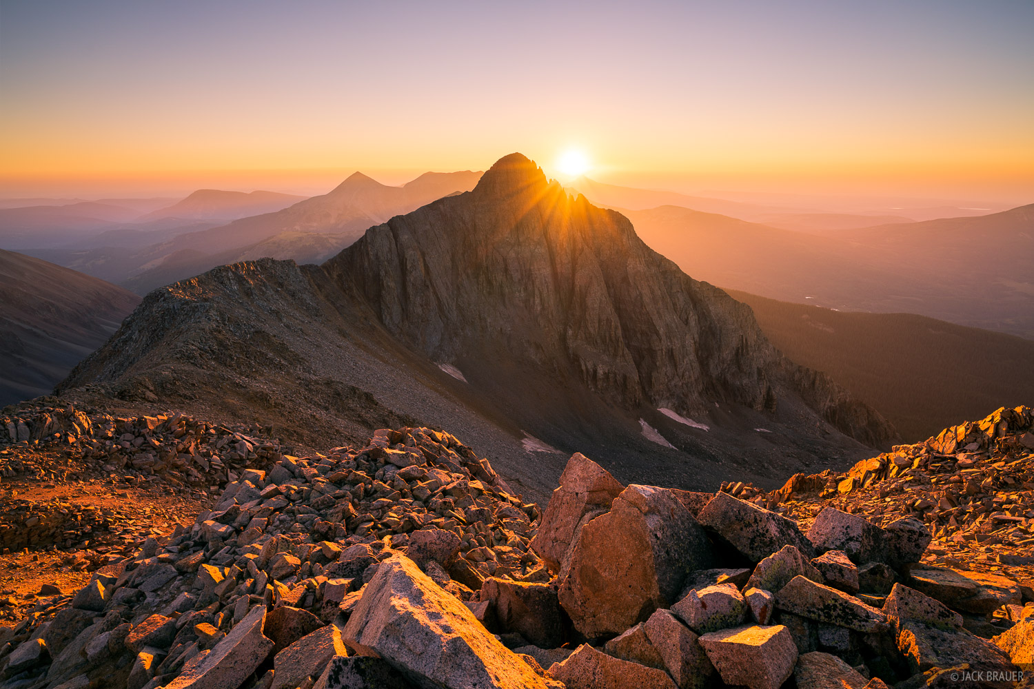 A brilliant sunset behind Fowler Peak (13,498 ft.) high up in the San Miguel Range - September. This rugged mountain is named...