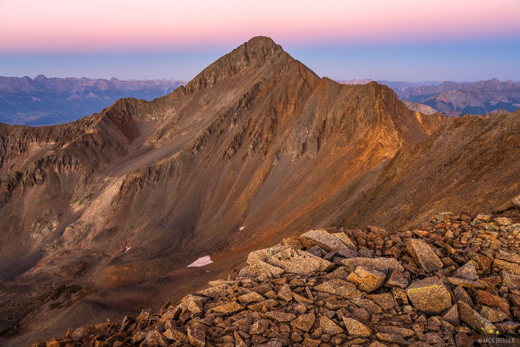 Dusk light illuminates the northwest face of Wilson Peak (14,016 ft.) and the Rock of Ages saddle below.